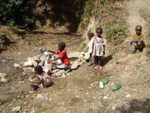Children gathering water from unprotected water source in Bayonnais, Haiti