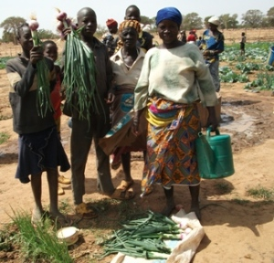 Family in Burkina Faso with vegetables harvested from garden