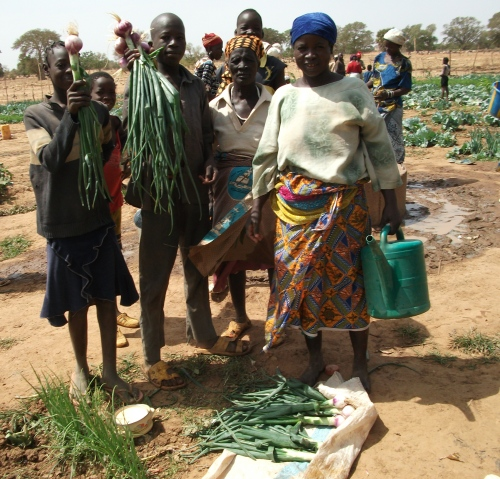 Family with locally harvested vegetables in Burkina Faso.
